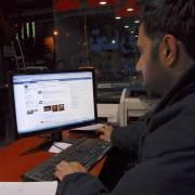 شاب سوري يتصفح موقع فيسبوك على شبكة الإنترنت.